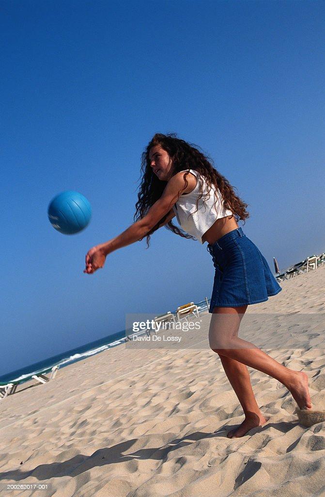 Teenage girl (16-17) playing beach volleyball