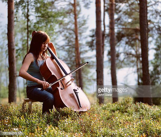 Teenage girl (13-15) playing cello in field