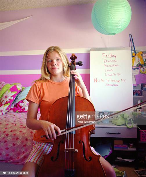 Teenage girl (14-15) playing cello in her room, portrait