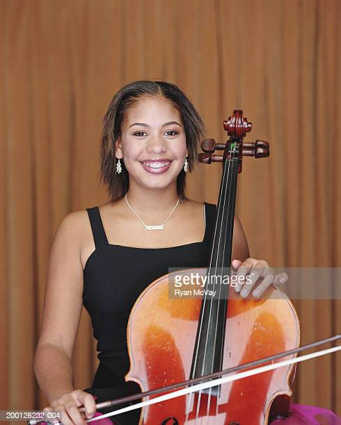 Teenage girl (13-15) playing cello, smiling, portrait