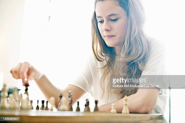 Teenage girl playing chess