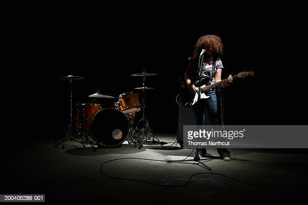 Teenage girl (13-15) playing electric guitar, drum kit in background