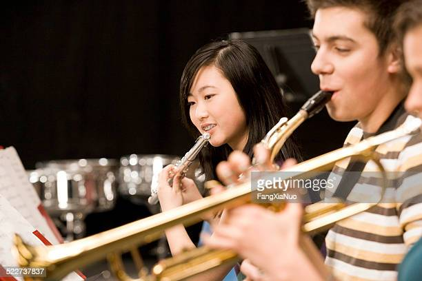Teenage girl playing flute in high-school band