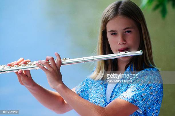 Teenage Girl Playing Flute Outdoors