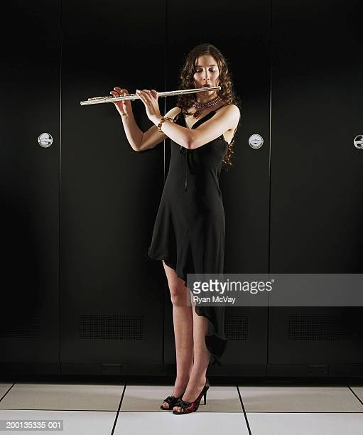 Teenage girl (16-18) playing flute, standing in server room