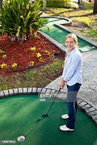 Teenage girl playing miniature golf