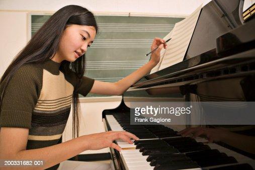 Teenage girl (12-14) playing piano, holding pen to sheet music : Foto de stock