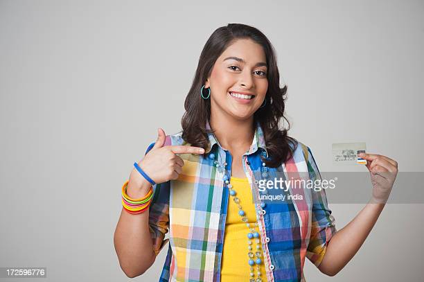Teenage girl pointing at a credit card and smiling