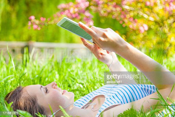 10 代の少女のポートレート、e -reader 屋外夏の公園