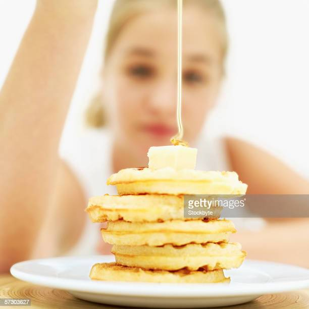 Teenage girl (15-17) pouring syrup on a stack of waffles (blurred)