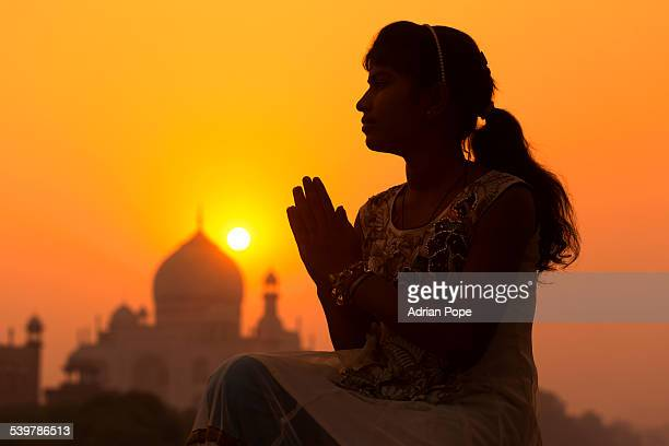 Teenage girl praying  with Taj Mahal in distance