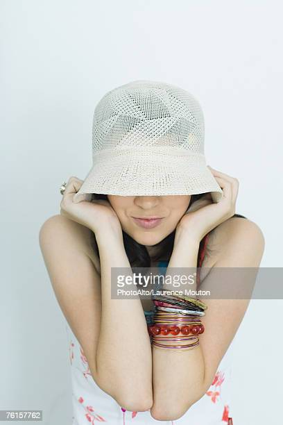 'Teenage girl pulling hat down over eyes, portrait'