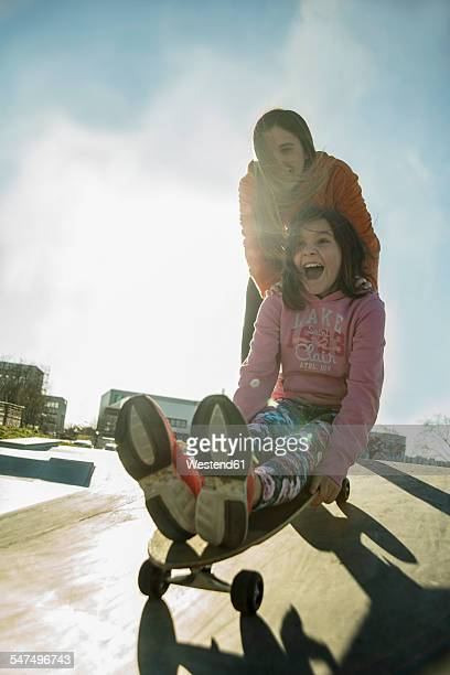 Teenage girl pushing girl on skateboard