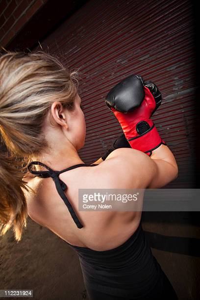 A teenage girl puts on a boxing glove before training for mixed martial arts outside a warehouse in Birmingham, Alabama.