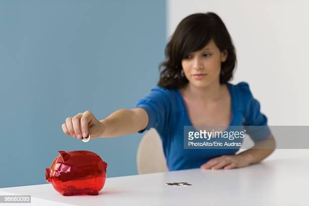 Teenage girl putting coin in piggy bank