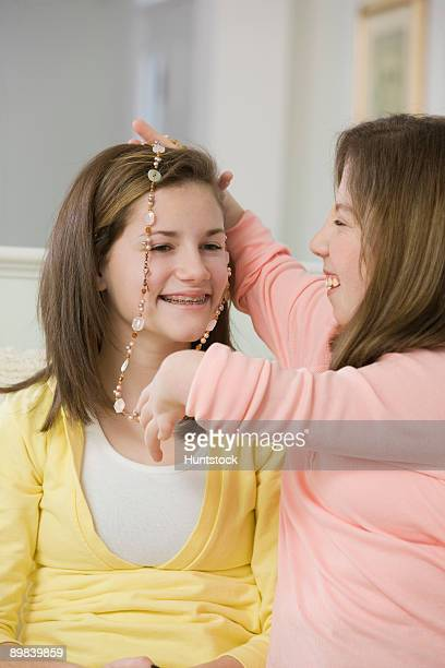 Teenage girl putting on a necklace on her sister