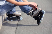 Teenage girl (14-16) putting on inline skates, low section