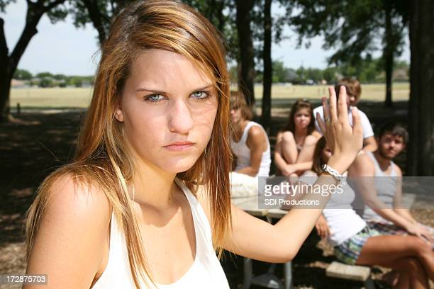 Teenage Girl Putting Up her Hand To Group Of Peers