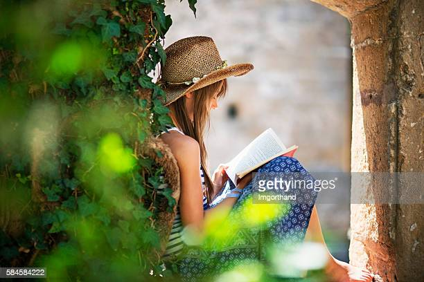 Teenage girl reading a book in old garden.