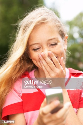 A teenage girl reading a message on her mobile phone.