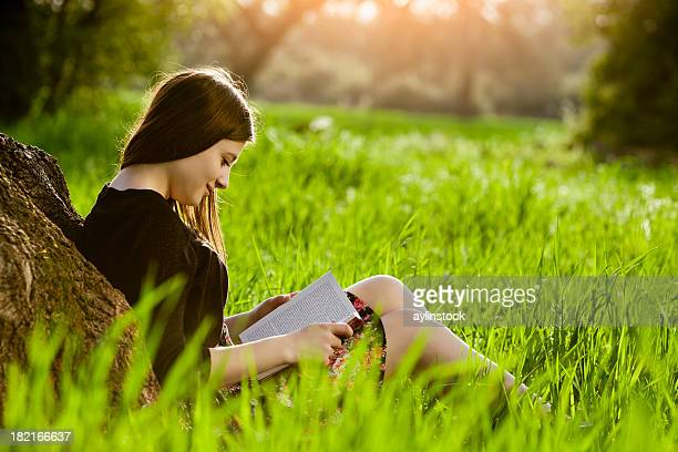 Teenage girl reading book on meadow