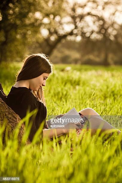 Jeune fille lisant un livre sur prairie