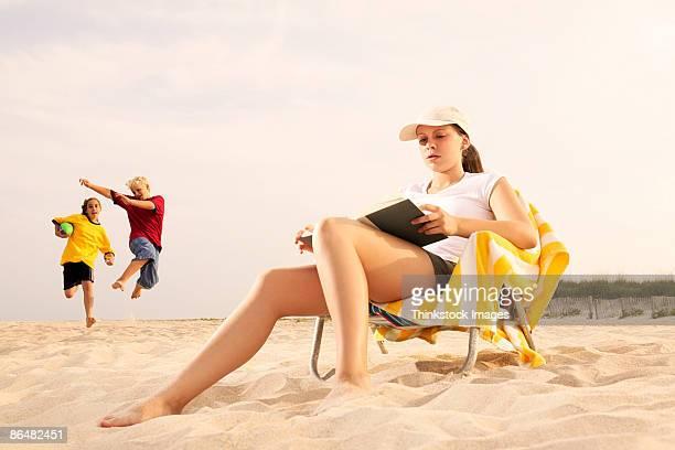 Teenage girl reading on beach
