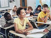 Teenage girl (15-17) receiving graded homework in class, smiling
