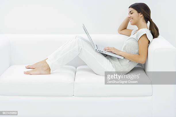 Teenage girl reclining on couch, using laptop, side view