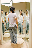 Teenage girl reflecting in front of mirror
