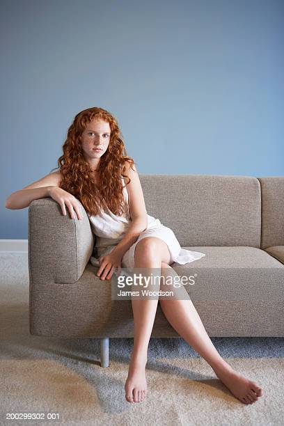 Teenage girl (13-15) relaxing on sofa, legs crossed, portrait