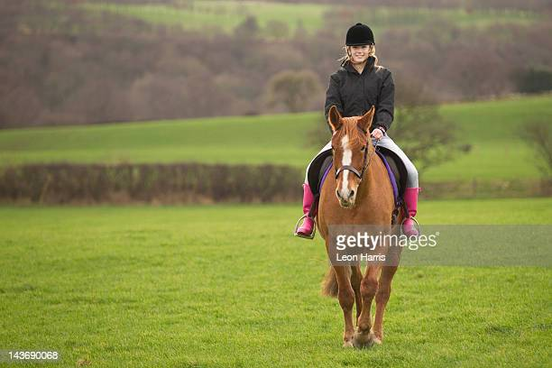 Teenage girl riding horse in field