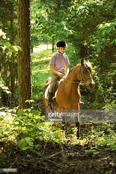 Teenage girl riding horse