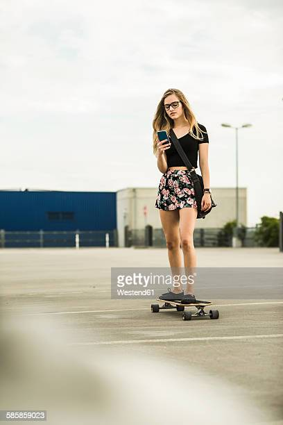 Teenage girl riding skateboard looking on cell phone