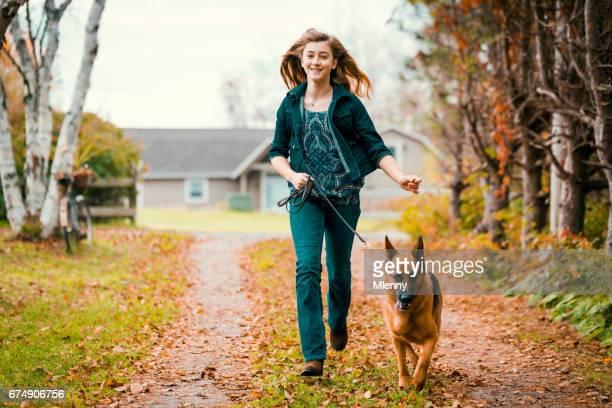 Teenage girl running with shepherd dog on a beautiful autumn day