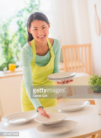 Teenage girl setting table : Stock Photo