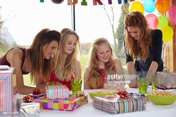 Teenage girl sharing birthday cake with friends