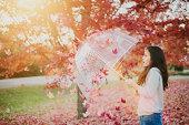 Teenage girl shielding herself from blowing leaves