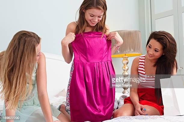 Teenage girl showing dress to friends