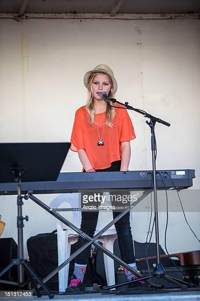 Teenage girl singing and playing keyboards