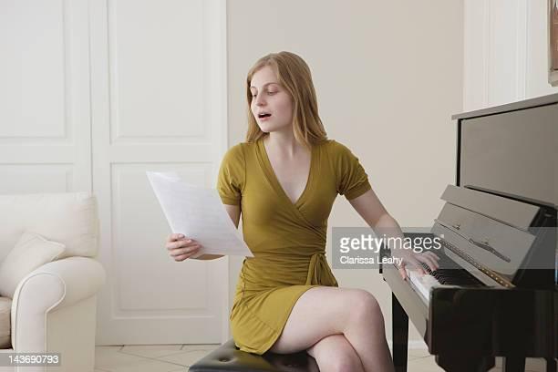 Jeune fille chantant et jouant du piano