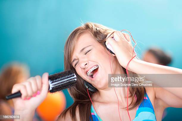 Teenage girl singing into hairbrush