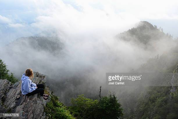 Teenage girl sitting alone in misty Smoky Mountains National Park