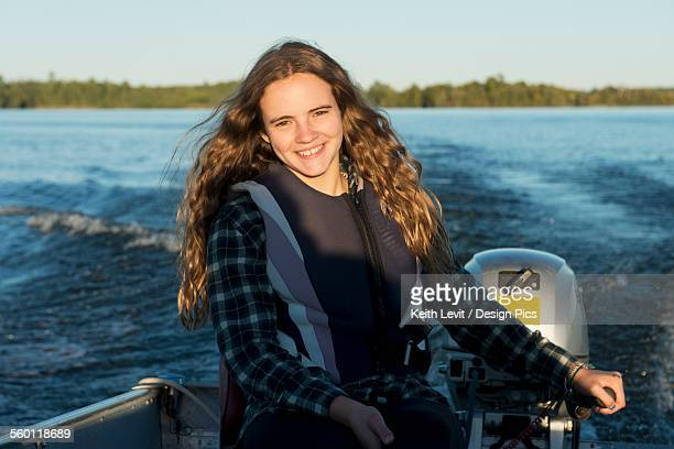 A teenage girl sits by the motor at the back of a motorboat with her face illuminated by sunlight