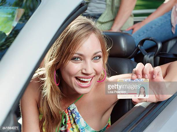 Teenage Girl Sits in the Driving Seat of a Convertible Car Holding an ID Card