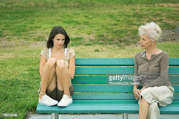 Teenage girl sitting apart from grandmother on bench, both frowning