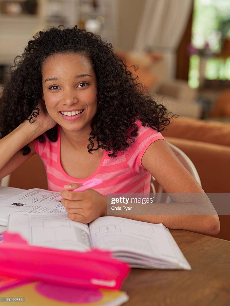 Teenage girl sitting at table doing homework smiling : Stock Photo