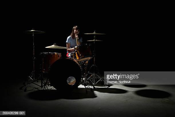 Teenage girl (14-16) sitting behind drum kit