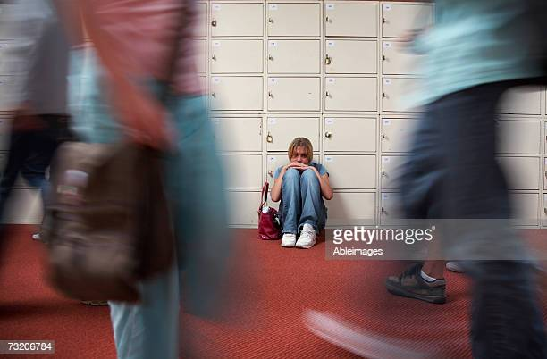 Teenage girl (13-15) sitting by lockers in school hallway