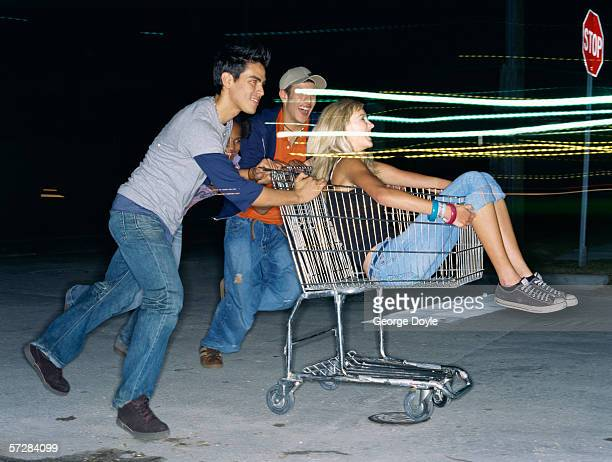 Teenage girl sitting in a trolley being pushed by Teenage boys